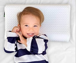 Toddler boy lying on pillow in bed - thumbnail