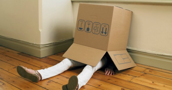 child sitting on floor with cardboard box over head