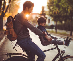 Father doubling small son on handlebars of bicycle without helmets