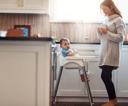 Mother feeding baby in highchair breakfast in the kitchen - feature