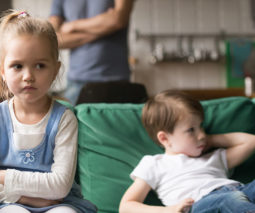 Siblings unhappy and fighting sitting on couch with parents in background - feature