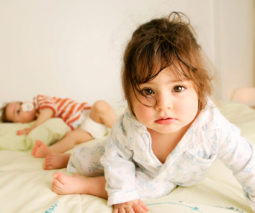 Two toddlers in pyjamas on bed - feature
