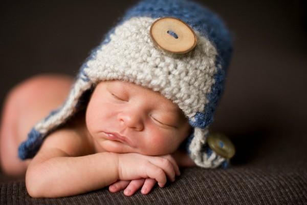 Sleeping newborn baby boy in crocheted hat