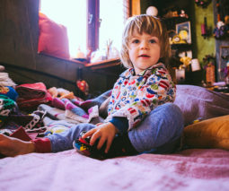 Toddler boy sitting on bed in pyjamas - feature