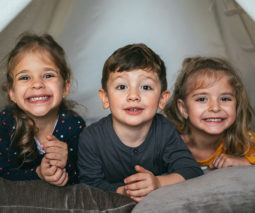 Three children in homemade tent with pillows - feature