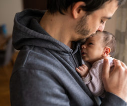 Young father in hoodie holding newborn baby - feature