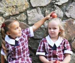 Two young school girls with an apple feature