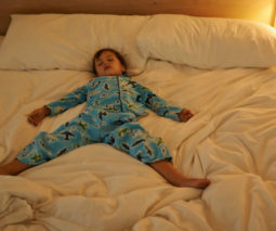 Toddler asleep spread-eagle in parent's bed - feature
