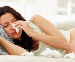 Pregnant woman lying on couch crying - feature
