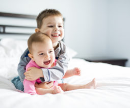 Toddler boy and baby girl hugging on bed - feature