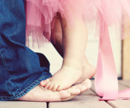 Toddler girl dancing on dad's feet with tutu - feature