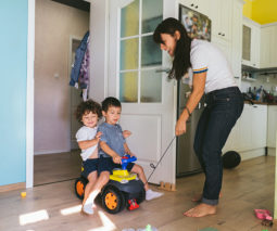 Mother playing with two boys with toy car - feature