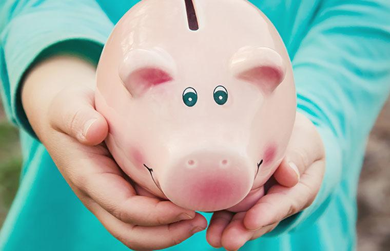 Child holding piggy bank money box - feature