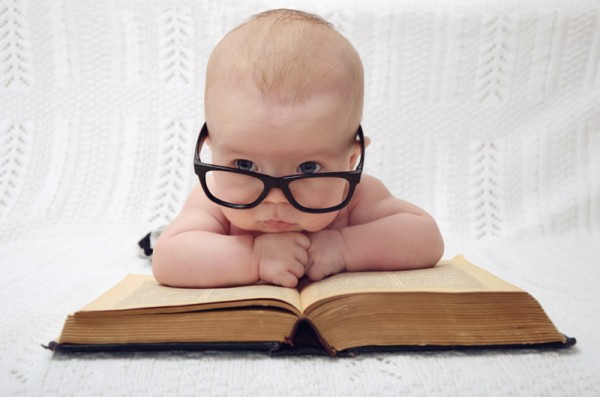 baby wearing oversized sunglasses with a large open book