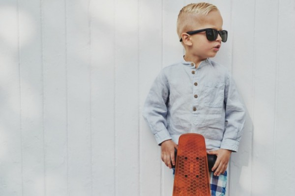 young boy with sunglasses holding a skateboard