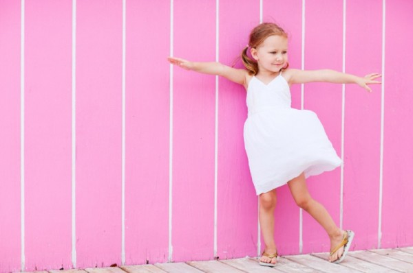 girl in white sundress standing in front of pink striped wall