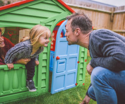 Father playing with girl and mother in cubby house - feature