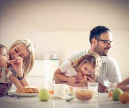 Family sitting at table and talking with kids feature