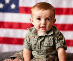 Baby boy sitting in front of US flag - feature
