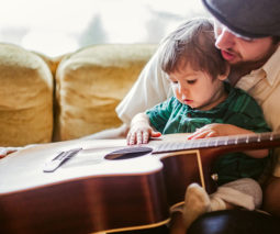 Father and toddler boy playing guitar together - feature