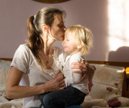 Mother sitting on bed kissing blonde toddler -feature