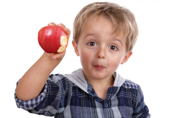 Healthy eating childhood nutrition concept small boy eating a red apple