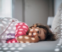 Toddler girl lying in bed smiling - feature