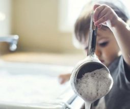 Toddler with washing up and saucepan - feature