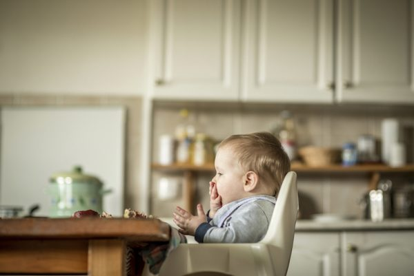 Portrait of happy baby boy in high chair and eating pomegranate