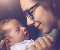 Mother wearing glasses holding newborn - feature