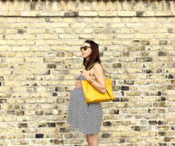 Pregnant woman walking past brick wall - feature