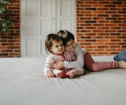 Girl sibling hugging baby sister - feature