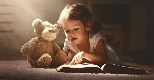 Child reading book to teddy