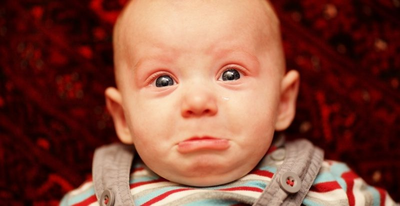Sad baby is crying