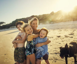 Mother hugging three children at beach with dog - feature