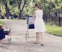 Mother and toddler girl pushing prams - feature