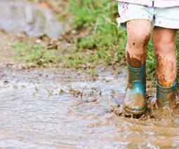 Toddler legs standing in gumboots in mud puddle - feature