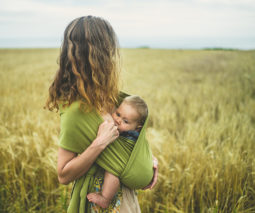 Mother breastfeeding baby in a sling standing in a field - feature