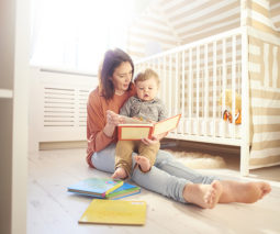 Mother sitting on floor with baby in lap reading books - feature