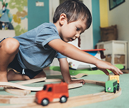 Boy playing with toy train and tracks - thumbnail