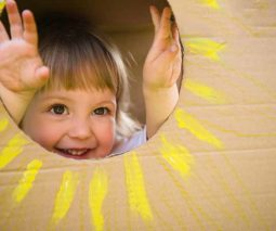 Young girl playing in cardboard box - feature