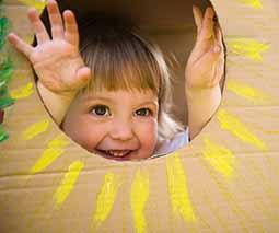 Young girl playing in cardboard box - thumbnail
