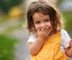 Laughing toddler girl covering her mouth - feature