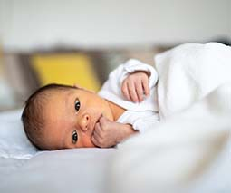 Newborn baby lying on side awake - thumbnail