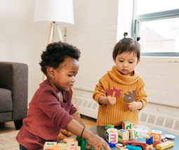 Two toddlers playing together with toys on a table - feature