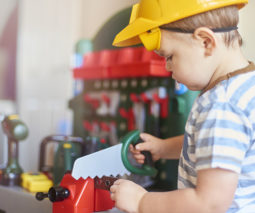 Toddler boy playing dress up as builder with hard hat and tools - feature