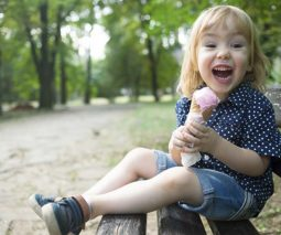 Toddler sitting in park eating an ice cream happy - feature
