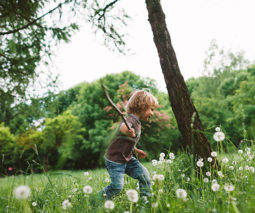 Boy running in a field holding a stick - feature