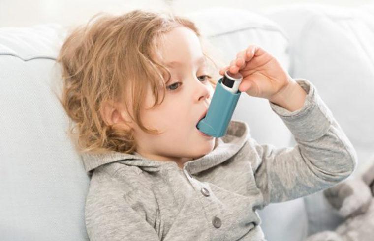 Child using asthma inhaler - feature