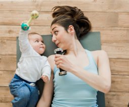 Mother and baby lying on exercise mat with hand weights - feature
